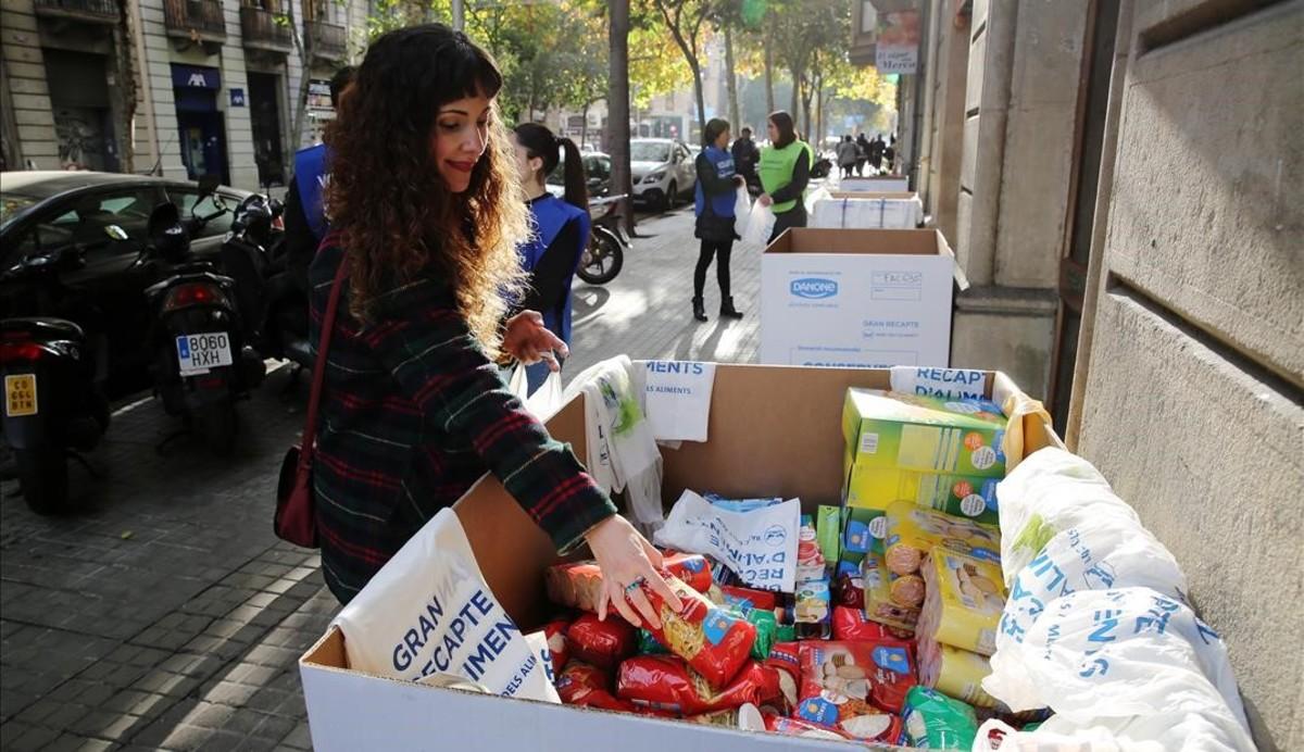 Una joven deposita alimentos en uno de los contenedores de la campaña situado en la calle de Consell de Cent de Barcelona.