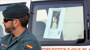 Un guardia civil con la foto que se ha distribuido de Diana Quer.