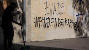 Un hombre barre el suelo ante un grafiti que reivindica la 'evasión', en una calle de Santiago de Chile.