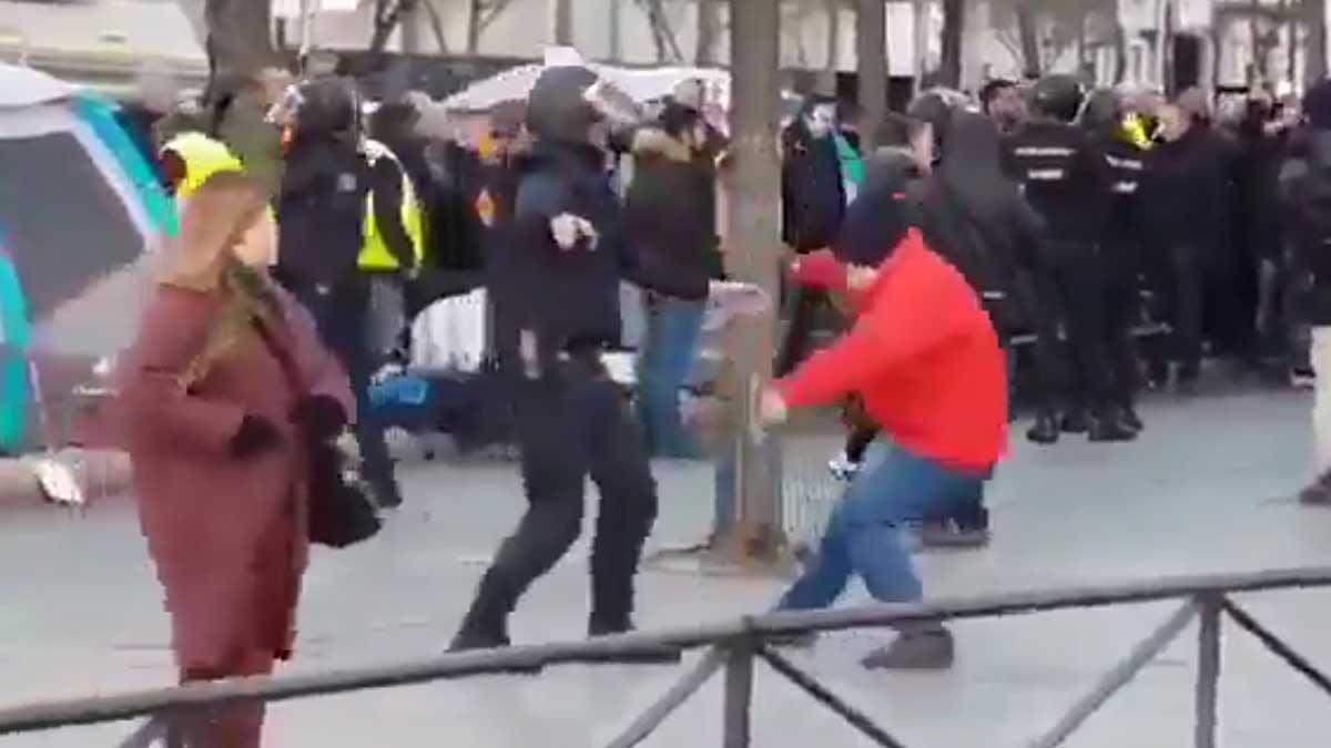 Un hombre se cae, o se tira, al suelo cuando un agente de la Policía Nacional le toca el brazo.