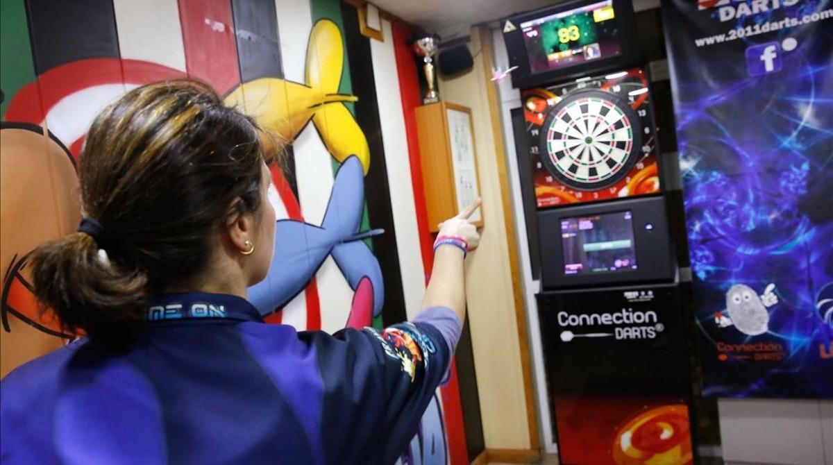Una jugadora tira un dardo en un bar de Santa Coloma. La partida forma parte de una liga local. La diana a la que apunta está conectada a internet. Las tiradas se pueden seguir por el móvil.