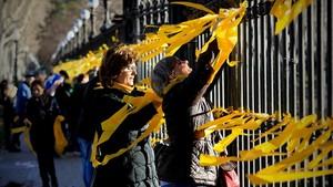 Varias personas colocan lazos amarillos en el parque de la Ciutadella de Barcelona