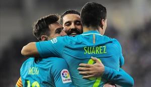 Leo Messi y Arda Turan felicitan a Luis Suárez, autor de un gol.