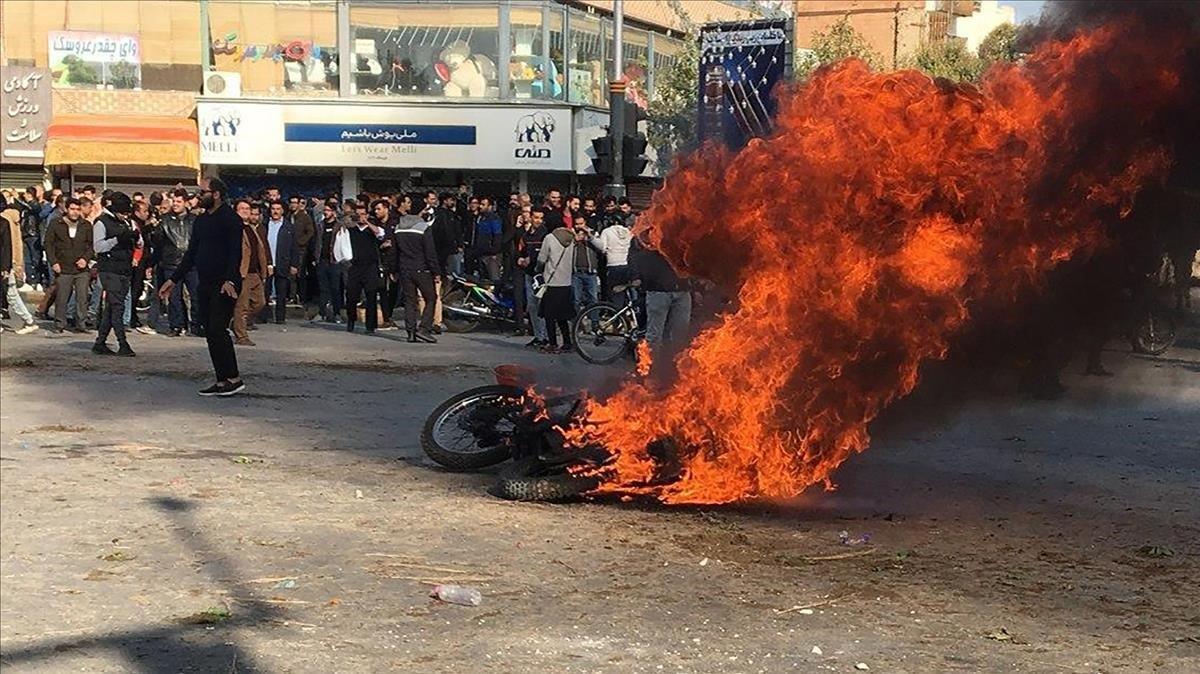 Manifestantes iranís junto a una motocicleta quemada en Isfahan (Irán).