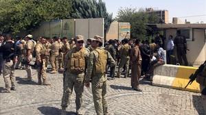 Miembros de las fuerzas de seguridad kurdas fuera del edificio gubernamental asaltado.