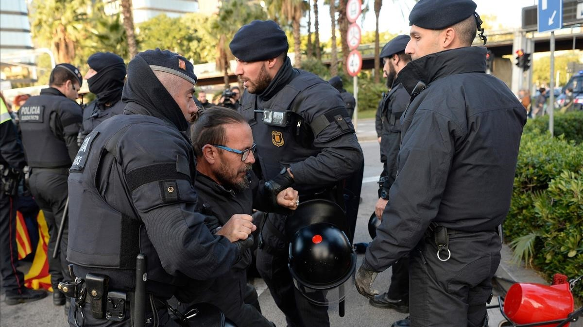 Mossos dEsquadra desalojan a los manifestantes que impiden el tráfico en la plaça Cerdà de Barcelona.