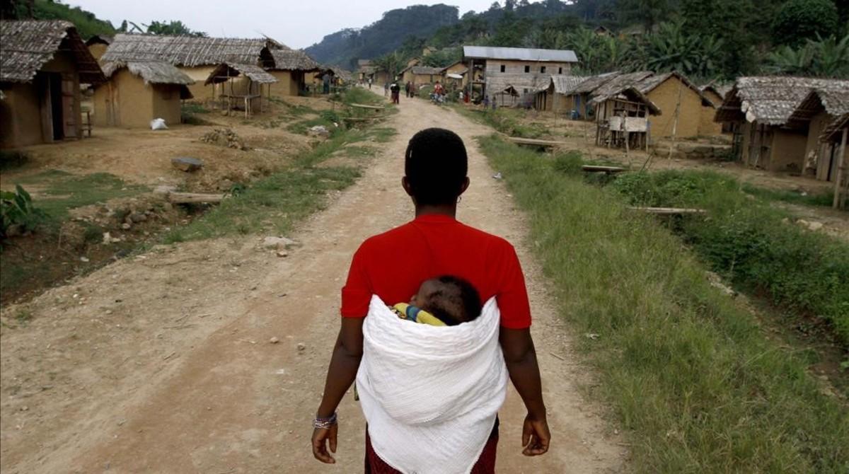 Una mujer congoleña camina con su hijo en la espaldahacia la aldea de Luvungi.