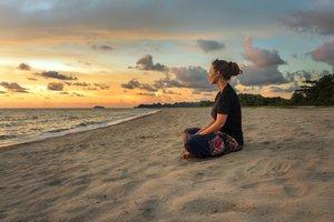 Mujer sentada en la playa.