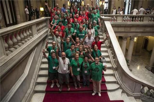 Representantes de la PAHcelebrando las ILP de medidas urgentes sobre vivienda y pobreza en las escaleras del Parlament el 9 de julio.