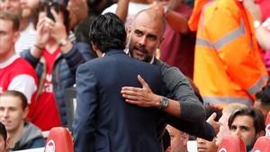 Pep Guardiola y Unai Emery (de espaldas) se saludan antes del Arsenal-Manchester City.