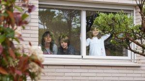 Tres hermanos de Igualada miran por la ventana de su casa durante el confinamiento, el pasado 21 de abril.