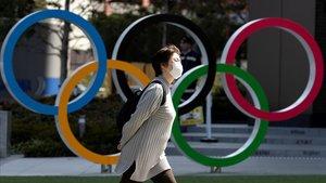 Una mujer con una máscara pasa frente a un símbolo olímpico en Tokio.