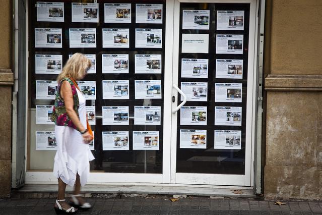 Una senyora passa davant d'una oficina de lloguers de pisos, a Barcelona.
