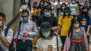 Usuarios del metro de Pekín con mascarillas bajan las escaleras en una estación de la capital china.