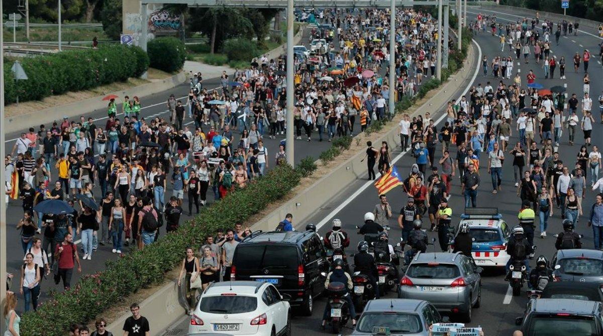 Manifestantes y viajeros caminan por la autopista camino del aeropuerto de El Prat.