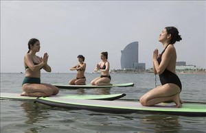 Clase de sup yoga sobre tabla de surfen la playa de Barceloneta de Surf House y Moritz, impartida por Eli Merino, en julio del 2016.