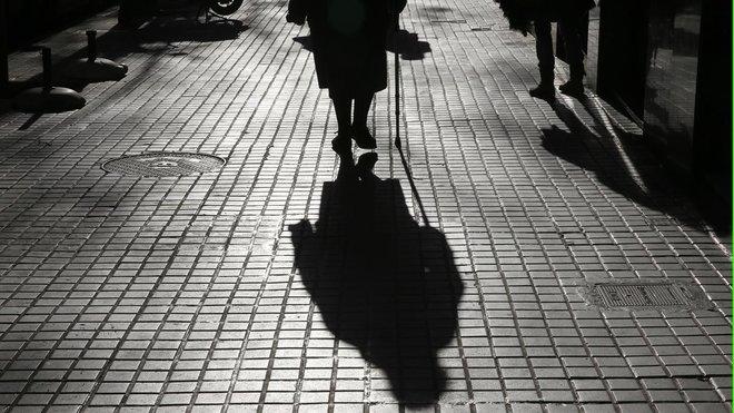 Una anciana camina en solitario por Barcelona.