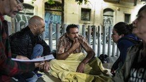 Carlos, voluntario de Arrels, habla con Navdeepsingh, antes de que la Guàrdia Urbana le expulse de esta plaza.