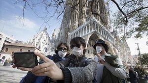 Unos turistas se hacen fotos en la Sagrada Família, cerrada al público debido al coronavirus.