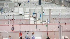 Un grupo de pacientes con covid-19 descansa en el recinto de IFEMA, habilitado como hospital temporal