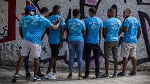 Algunas de las personas que llegaron a España a bordo del Aquarius posan con la camiseta con la que uno de ellos bajó del barco