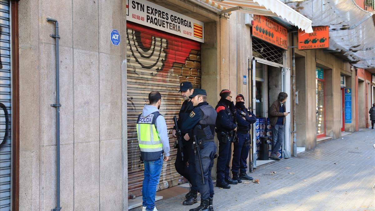 Policías custodian la entrada de uno de los locales investigados, en la calle de Espronceda.
