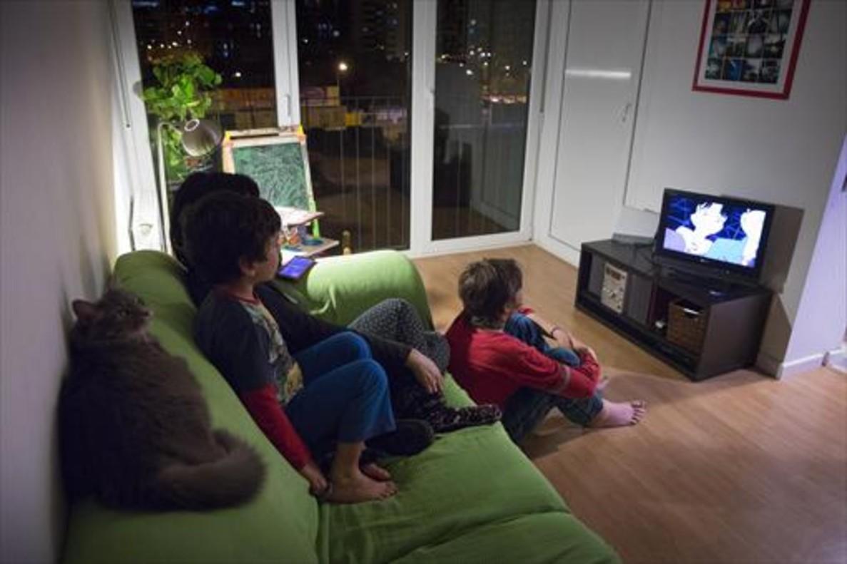Una familia, ante el televisor de su casa. Las cadenas, según la reforma horaria, deben avanzar su 'prime time'.