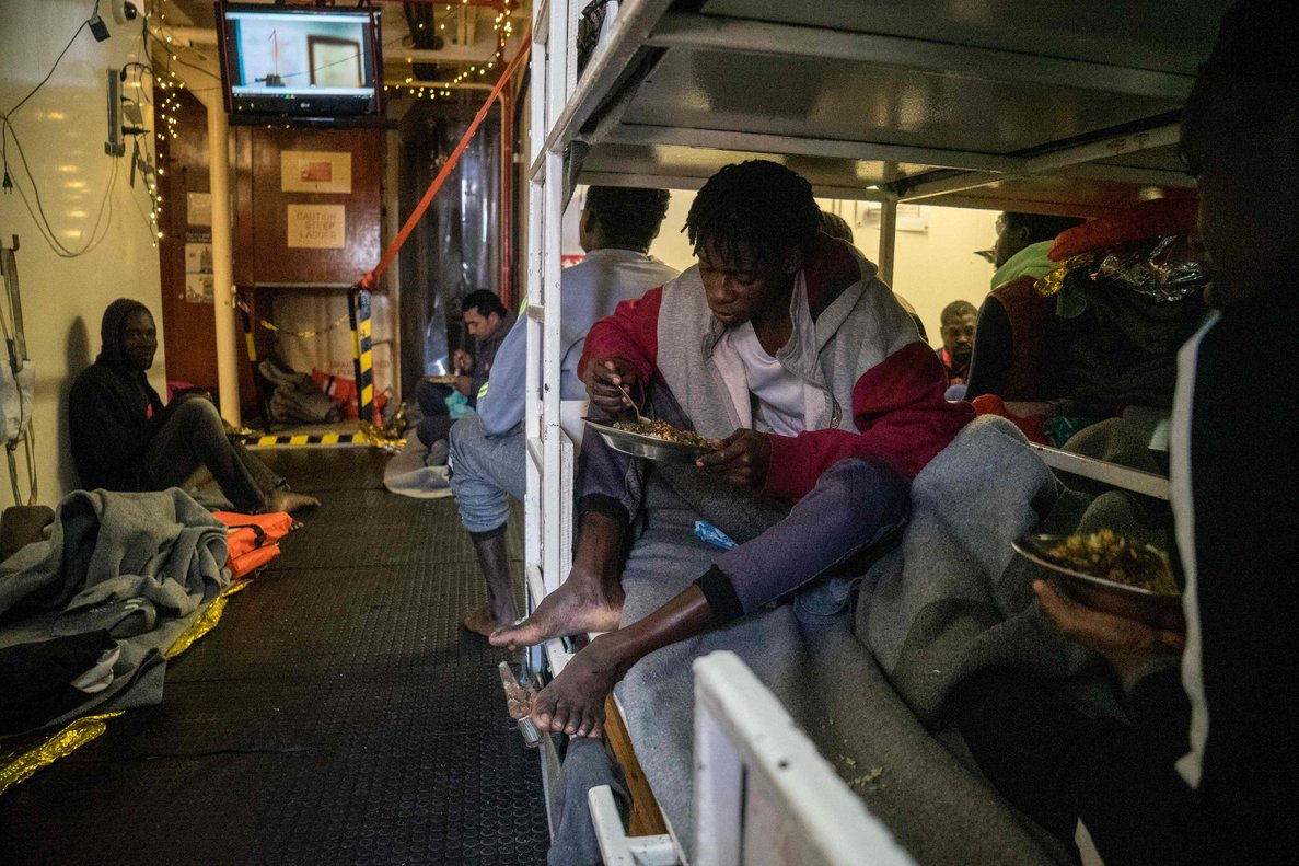 Rescued migrants eat a hot meal onboard the Dutch-flagged rescue vessel Sea Watchsailing the Mediterranean about 3 nautical miles off Malta s coasta day after Mediterranea and Sea-Watch launched two boats to deliver suppliesincluding fresh water-Photo by FEDERICO SCOPPAAFP