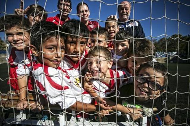 Alevines del modesto club Alzamora bromean tras las redes de una portería.