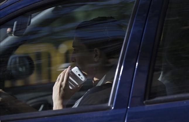 Un conductor usa el teléfono mientras circula por el Eixample de Barcelona.