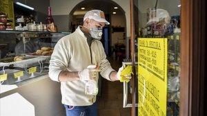 Un hombre desinfectala puerta de entrada de un negocio en la localidad deCodogno, en la región de Lombardía.