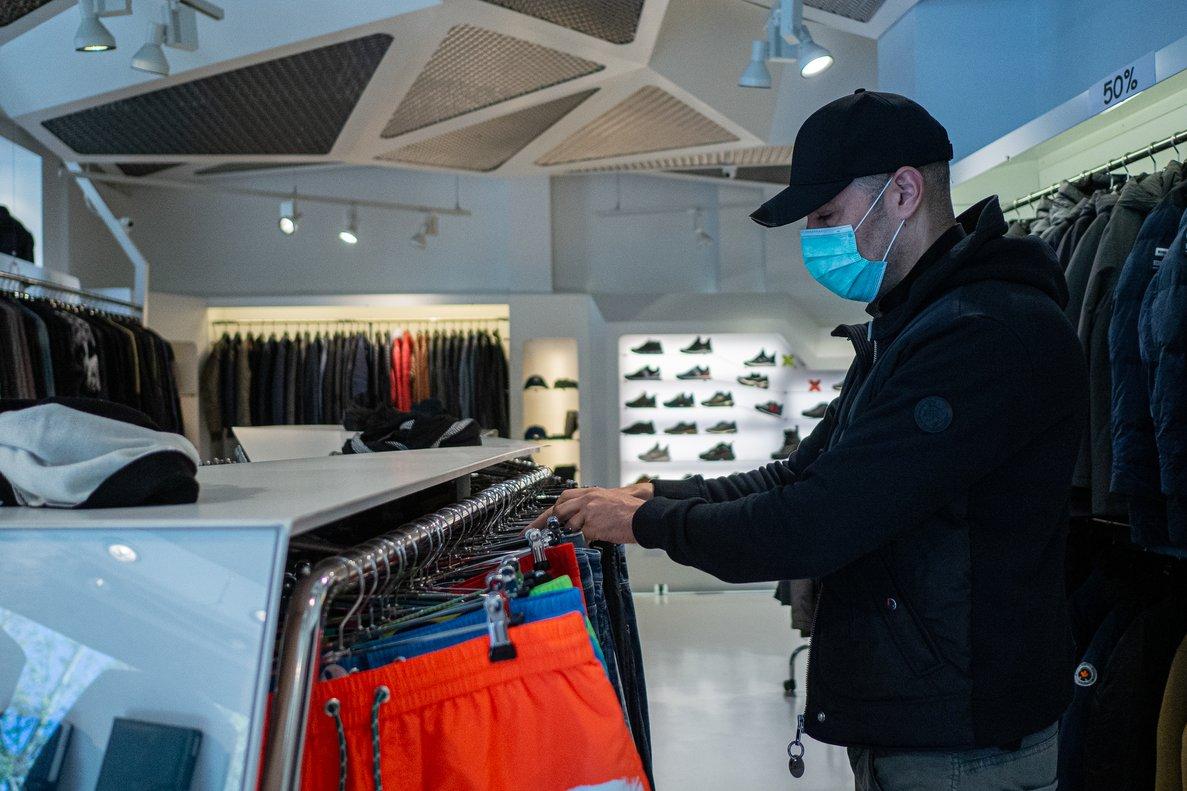 Un trabajador protegido coloca ropa en su establecimiento durante el tercer día en el que se permite la apertura del pequeño comercio.