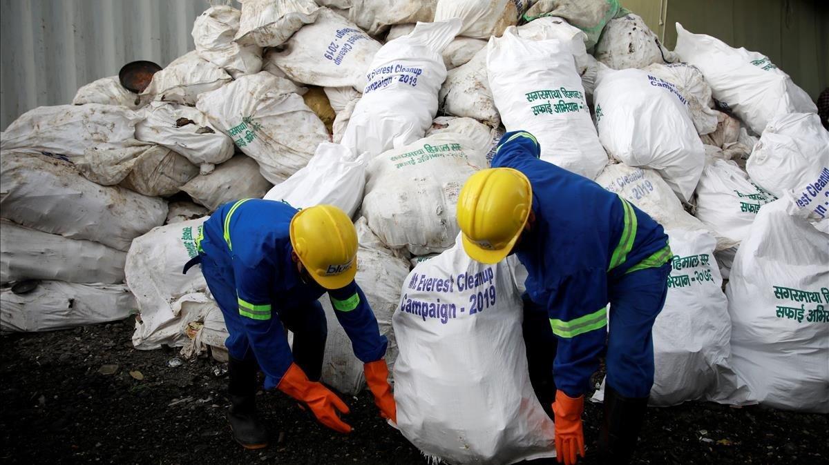 Empleados nepalís recogen basura recopilada en el Everest.