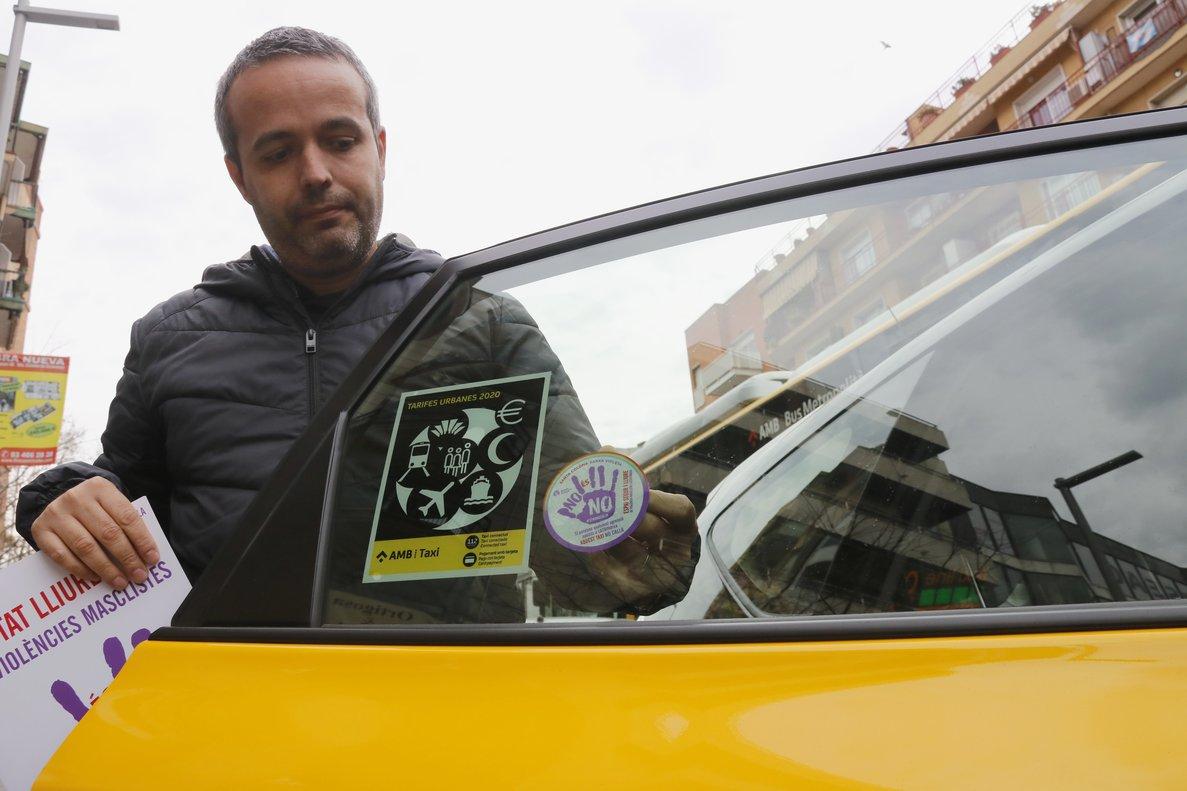 Un taxista coloca el distintivo de la 'red violeta' de Santa Coloma en su vehículo.