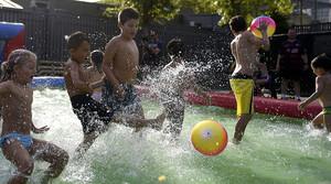 Un grupo de niños juegan al fútbol en una piscina inflable.
