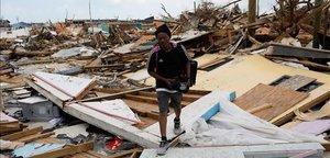 Un hombre camina por un vecindario devastado por el huracán 'Dorian' en las islas Abaco.