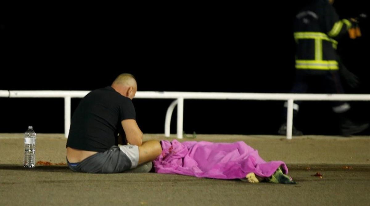Un hombre sentado junto a un cuerpo en el suelo, tras el ataque de Niza, este viernes.