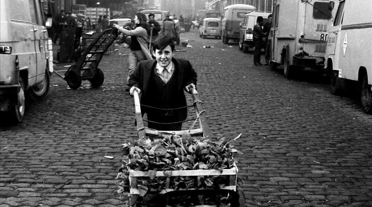 Un niño transporta verduras en una carretilla delante del Mercat del Born, en 1971.