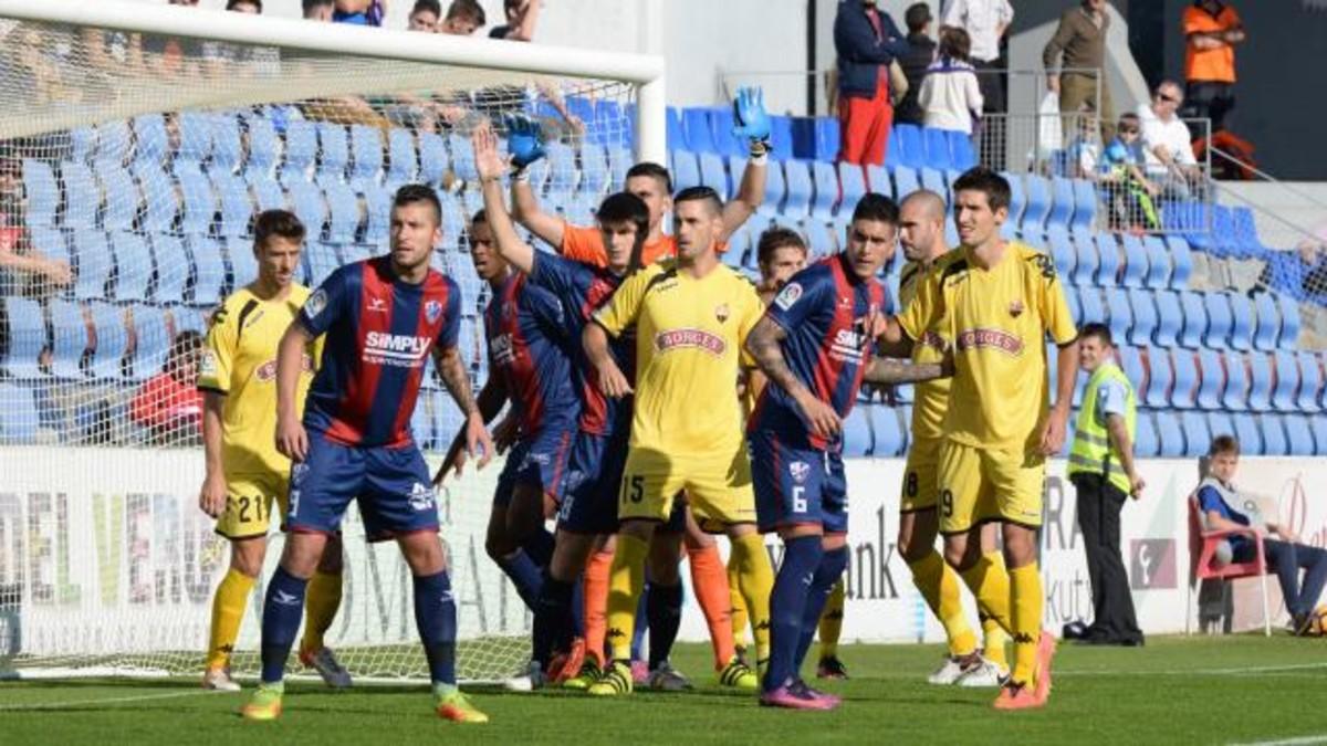 Los jugadores del Reus y del Huesca pugnan en el lanzamiento de un córner.