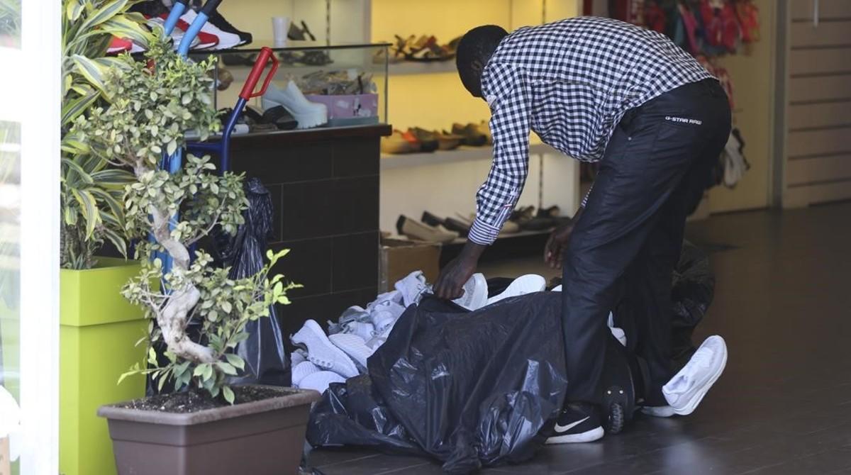 Un mantero carga una bolsa con decenas de zapatillas de deporte adquiridas a un mayorista chino ubicado en la avenida del Maresme del polígono Badalona Sud, el viernes.