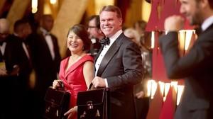 Martha Ruiz y Brian Cullinan, representantes dePreicewaterhouseCoopers, sostienen los maletines con los sobres ganadores en la gala de los Oscars.