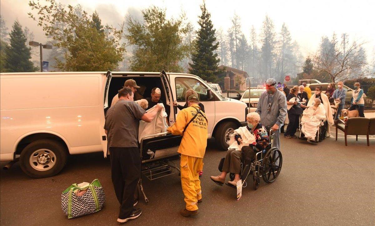 Miembros de los servicios de rescate trasladan a un grupo de personas lejos de los efectos de las llamas, en la localidad californiana de Paradise.