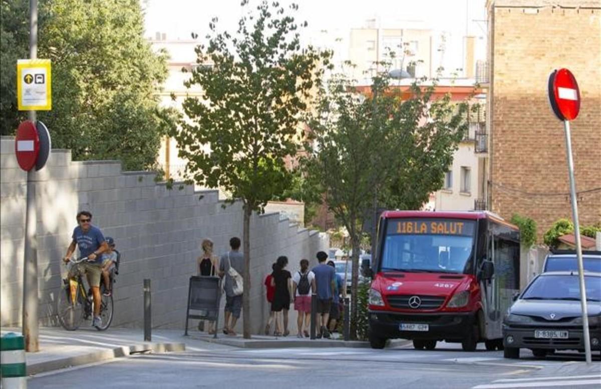 Unos turistas pasan a piejunto al autobús de la línea 116 en su camino hacia el parque Güell.