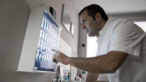 El odontólogo Carles Pejoan examina unas pruebas de TAC sobre implantes.