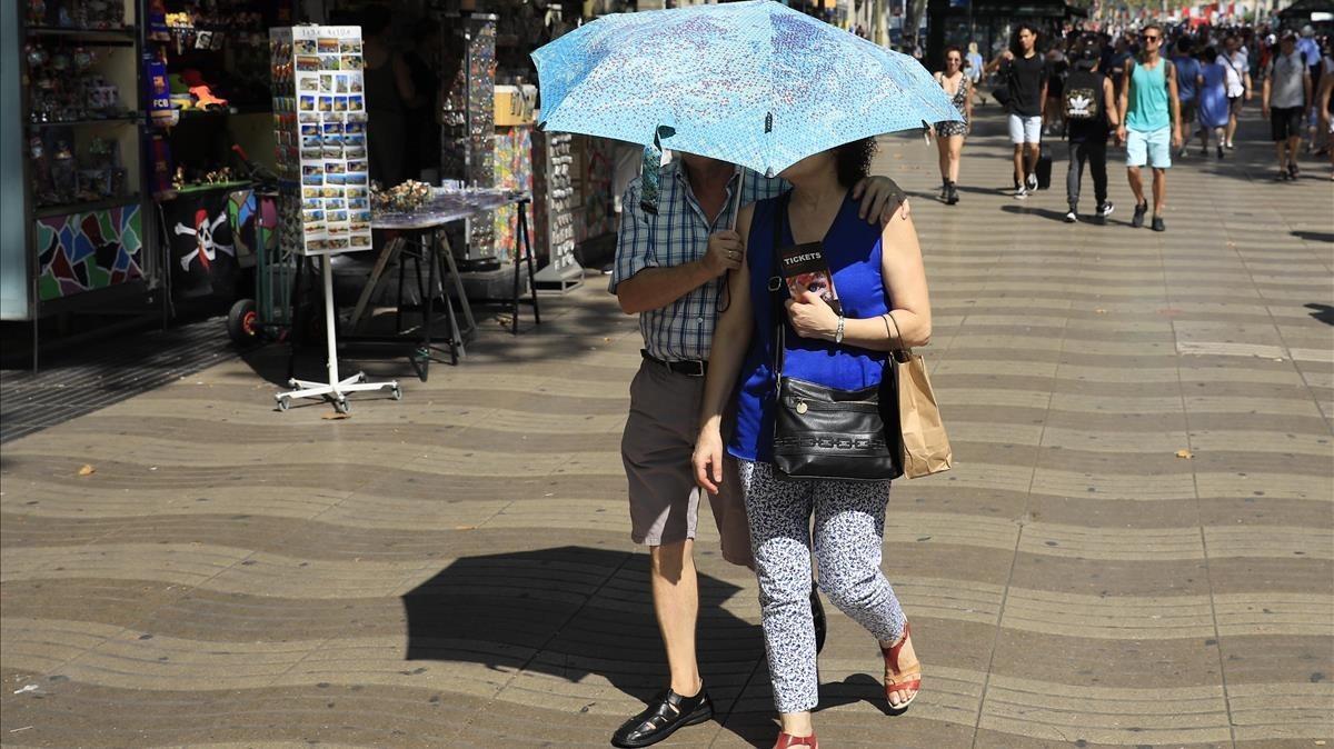 Una pareja se protege del sol con un paraguas en Barcelona.