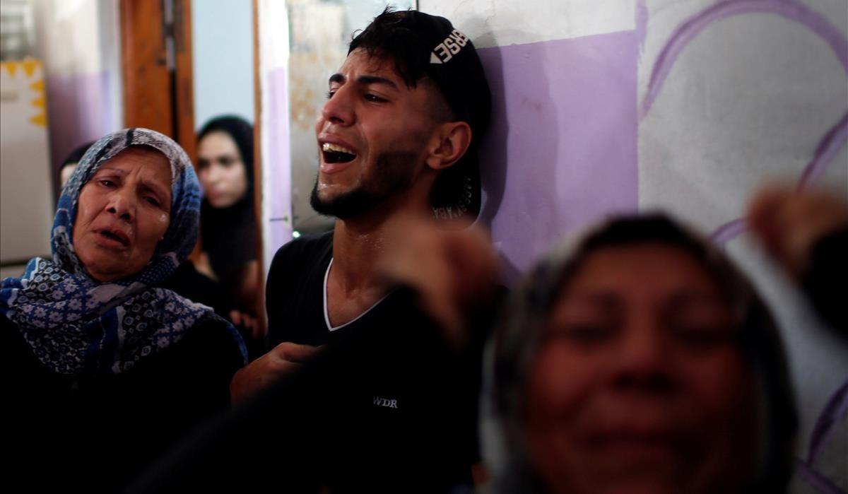 Palestinos, desgarrados por el dolor tras la muerte de unos familiares.