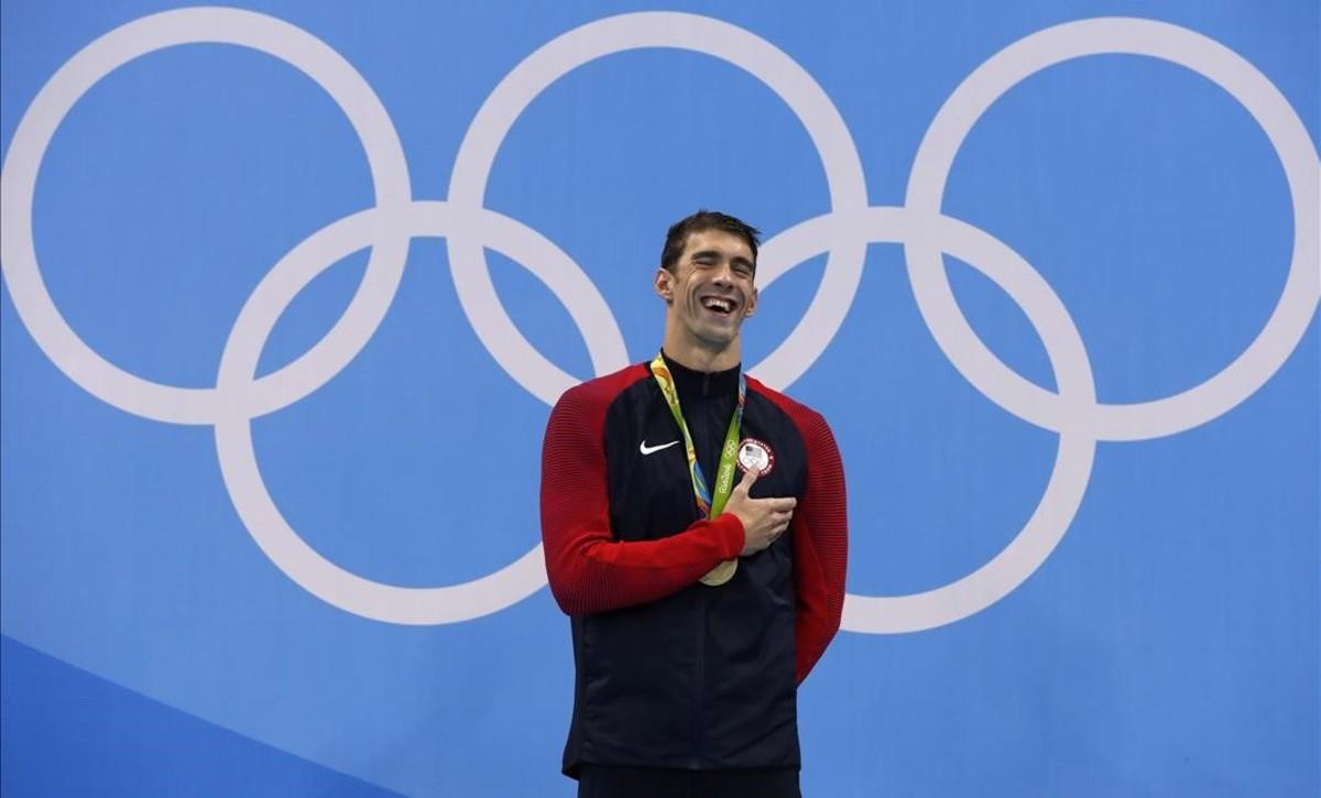 Phelps sonríe en el podio con el oro con el que recupera el título olímpico en los 200 mariposa
