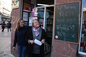 La propietaria de la librería Dumbo, Rosa Maria García, junto a la pizarra que anuncia que ha vendido el cuarto premio.