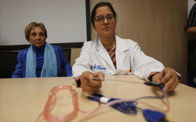 La doctora Elisabeth Pando (derecha) mostrando la aguja que se utiliza para la radiofrecuencia intraoperatoria.A la izquierda, lapaciente María José.