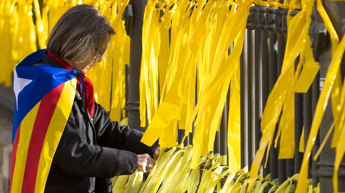 Una mujer coloca lazos amarillos en una verja en el parque de la Ciutadella en Barcelona, en una foto de archivo